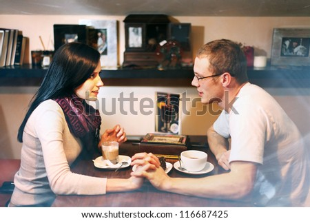 young lovers man and woman talking in the cafe - stock photo