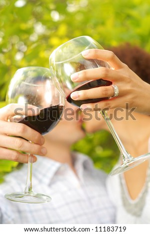 Young lovers on a romantic picnic outside, drinking wine and kissing