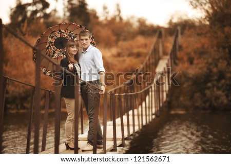 young lovers on a rope bridge across the river under the umbrella - stock photo