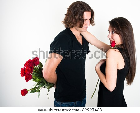 Young lovers on Valentines Day young man holding long stem red roses behind his back to give to his sweetheart. Girlfriend has one arm draped around his neck while holding a single rose - stock photo
