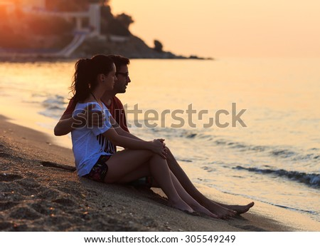 Young lovers sitting in the sand on shore at sunrise.