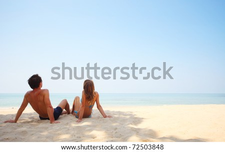 Young lovers sitting on sand and looking to a clear blue sky - stock photo