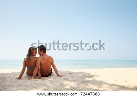 Young lovers sitting on sand near sea and looking to each other - stock photo