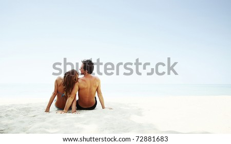 Young lovers sitting on warm sand at sunny day and enjoying each other - stock photo