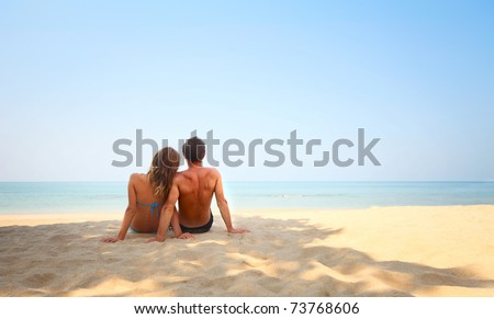 Young lovers sitting on warm sand at sunny day and looking to a clear blue sky - stock photo