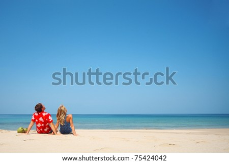 Young lovers sitting on warm sand at sunny day and looking to somewhere - stock photo