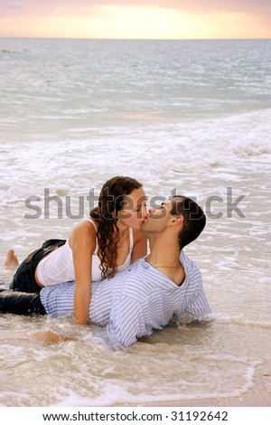 young lovers so wrapped up in their kissing they don't notice that the tide is rising around them as the sunsets - stock photo