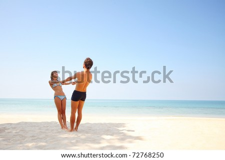 Young lovers standing on warm sand at sunny day and enjoying each other - stock photo
