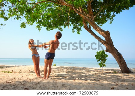 Young lovers standing under green tree holding each other hands - stock photo
