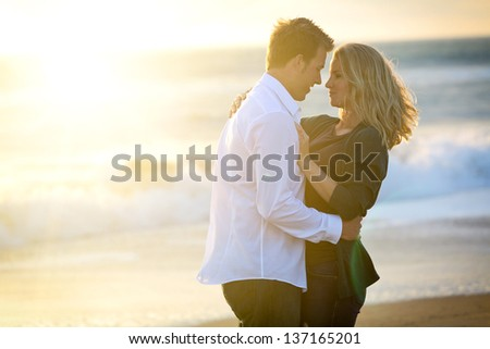 Young loving couple at the beach at sunset - stock photo