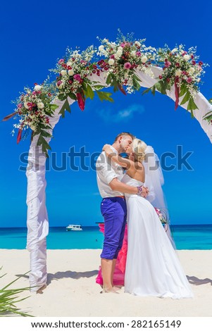 young loving couple, bride and groom, on their wedding day on wedding setup, arch, venue background