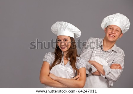 Young loving couple cooks. Over gray background - stock photo