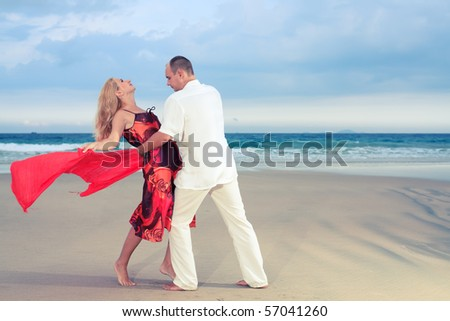 Young loving couple dancing at the beach
