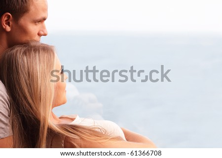 Young loving couple embracing and looking at a beautiful seaview in the window - stock photo