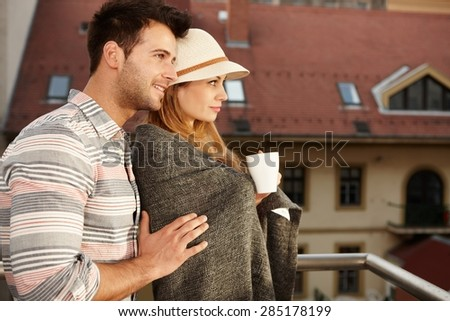 Young loving couple embracing in balcony. Side view. - stock photo