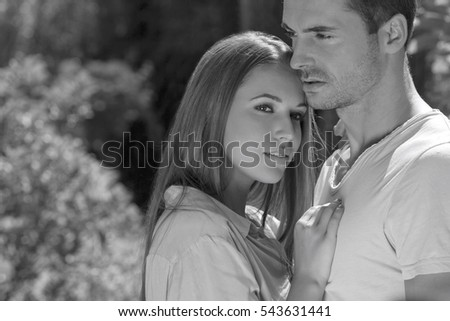 Young loving couple embracing in park