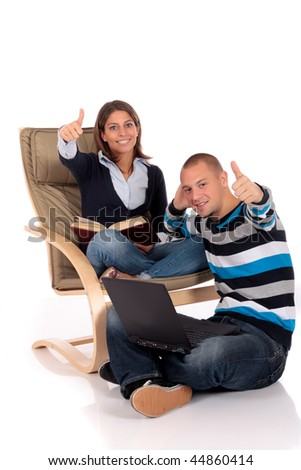 young loving couple grooming in sofa, reading book, listening music with headset, laptop for entertainment.  Studio.