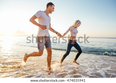young loving couple having fun on beach during sunrise or sunset