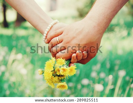 Young loving couple holding hands each other with bouquet of yellow dandelions in summer park, view of hands - stock photo