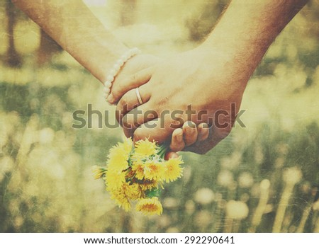 Young loving couple holding hands each other with bouquet of yellow dandelions in summer park, view of hands. Vintage image - stock photo