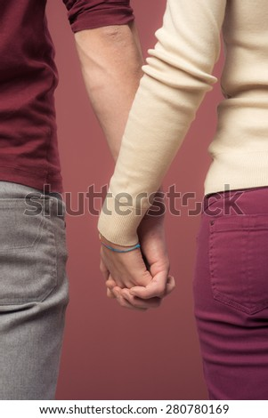 Young loving couple holding hands on red background - stock photo
