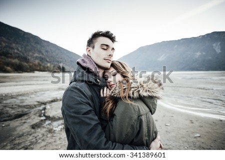 Young loving couple hugging, lake and mountains on background, love and romance concept - stock photo