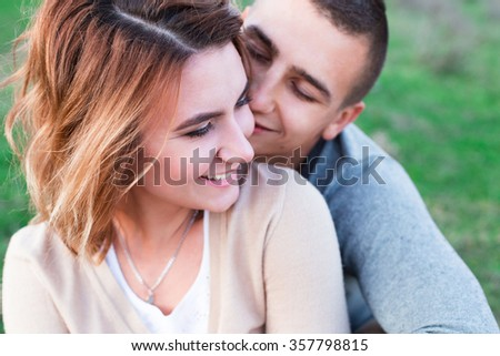 Young loving couple hugging outdoors on the green grass - stock photo