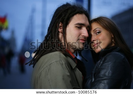 Young loving couple in a city at dusk.