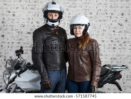 Young loving couple in a motorcycle outfit and helmets standing together near the street motorbike in the garage