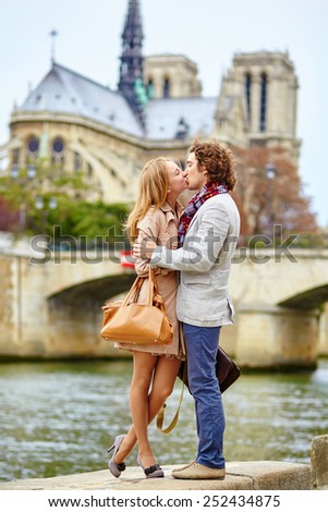 Young loving couple in Paris near Notre-Dame cathedral