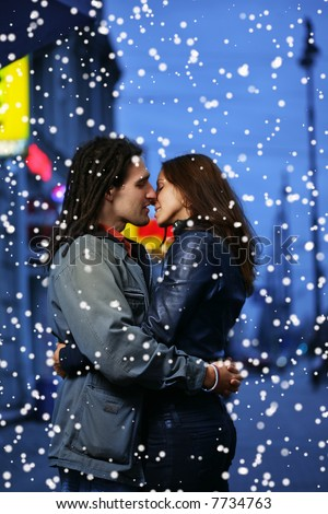 Young loving couple kissing in a winter city. - stock photo