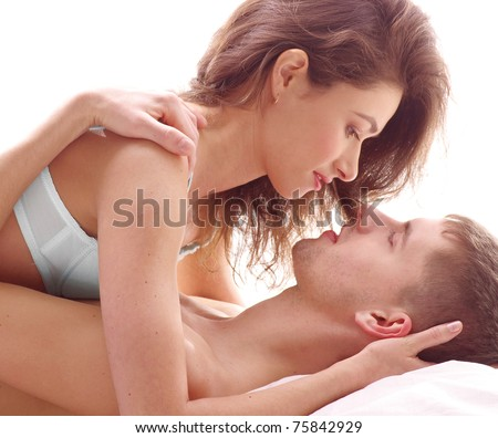 Young loving couple kissing in the bed isolated on white - stock photo