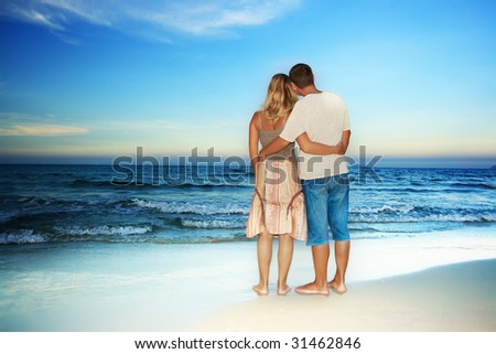Young loving couple looking to the ocean - stock photo