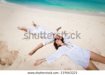 Young loving couple lying on caribbean beach, enjoying each other - stock photo