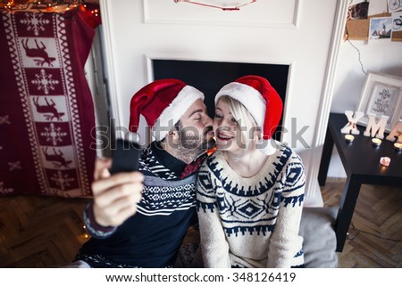 Young loving couple making selfie. Boyfriend kissing his girlfriend in the cheek. Christmas Time - stock photo