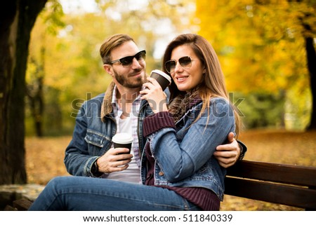 Young loving couple on a bench in autumn park and holding coffee to go in the hands