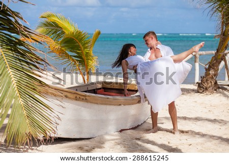 young loving couple on their wedding day, near the boat on the sand, outdoor beach wedding in tropics - stock photo