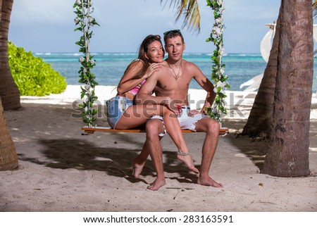 young loving couple on their wedding day, on the swing, outdoor beach wedding in tropics - stock photo