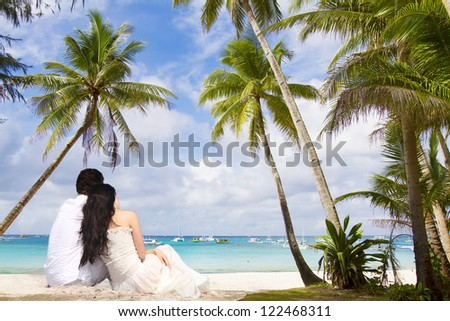 young loving couple on tropical sea background - wedding on beach - stock photo