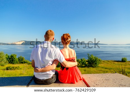 young loving couple people are looking at the sea and mountains