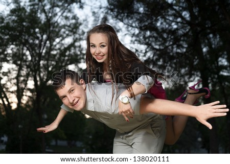 Young loving couple piggybacking in the park in the evening sunset - stock photo