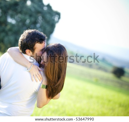 Young loving couple playing outside - stock photo