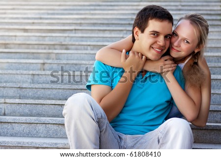 young loving couple sitting on stairs and embrace - stock photo