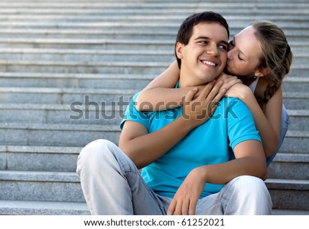 young loving couple sitting on stairs and embracing - stock photo