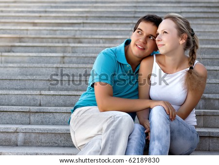 young loving couple sitting on stairs and looking in the sky - stock photo
