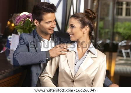 Young loving couple standing at reception desk, looking each other affectionate, smiling. - stock photo