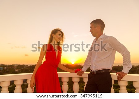 young loving couple standing next to the stone gazebo with the sunset in the background - stock photo