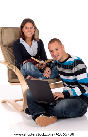 young loving couple, students,  grooming in sofa, reading book, laptop for entertainment.  Studio.