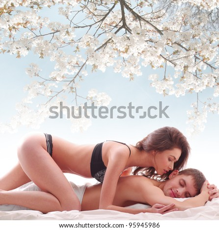 Young loving couple under the japanese cherry tree