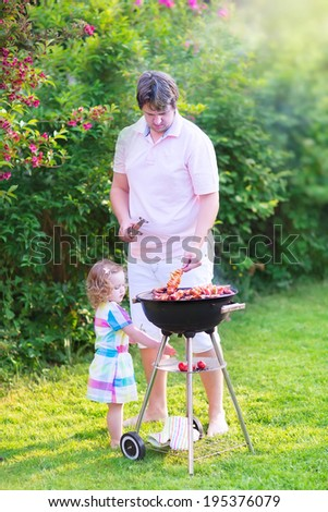 Young loving father and his cute happy toddler daughter, adorable curly girl wearing a colorful dress, having fun together grilling meat and vegetables in a sunny garden on a hot summer day - stock photo